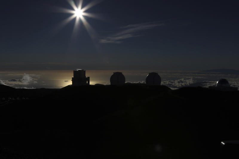 The sun sets behind telescope at the summit of Hawaii's Mauna Kea, Sunday, July 14, 2019. Hundreds of demonstrators are gathered at the base of Hawaii's tallest mountain to protest the construction of a giant telescope on land that some Native Hawaiians consider sacred. State and local officials will try to close the road to the summit of Mauna Kea Monday morning to allow trucks carrying construction equipment to make their way to the top. Officials say anyone breaking the law will be prosecuted. Protestors have blocked the roadway during previous attempts to begin construction and have been arrested. (AP Photo/Caleb Jones)