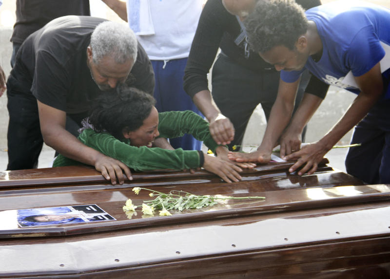A survivor cries on the casket of her sister who died when their boat capsized off in the Canal of Sicily before it is embarked on a Italian Navy ship at the Lampedusa island harbor, Saturday, Oct. 12, 2013. A fishing boat packed with 500 African migrants capsized on Thursday Oct. 3, 2013 off the shores of the island of Lampedusa, causing more than 300 dead. The enormous scale of the tragedy, which could become the largest death toll in a migrant shipwreck in the Mediterranean on record, has created momentum for a comprehensive European Union immigration policy to cope with the tens of thousands fleeing misery and strife in Africa and the Middle East. (AP Photo/Mauro Buccarello)