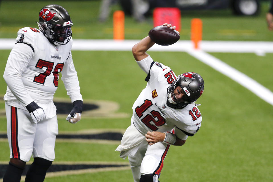 Tampa Bay Buccaneers quarterback Tom Brady (12) celebrates his touchdown with offensive tackle Donovan Smith (76) in the first half of an NFL football game against the New Orleans Saints in New Orleans, Sunday, Sept. 13, 2020. (AP Photo/Brett Duke)