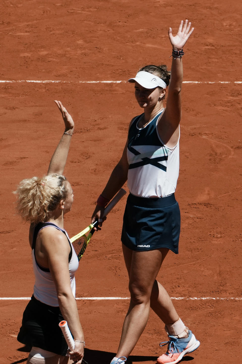 Czech Republic's Barbora Krejcikova, right, and compatriot Katerina Siniakova wave after they defeating USA's Bethanie Mattek-Sands and Poland's Iga Swiatek during their women's doubles final match of the French Open tennis tournament at the Roland Garros stadium Sunday, June 13, 2021 in Paris. (AP Photo/Thibault Camus)