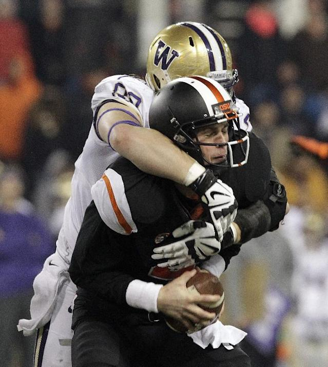 Oregon State quarterback Sean Mannion, right, is sacked from behind by Washington defender Evan Hudson during the second half of an NCAA college football game in Corvallis, Ore., Saturday, Nov. 23, 2013. Washington beat Oregon State 69-27. (AP Photo/Don Ryan)