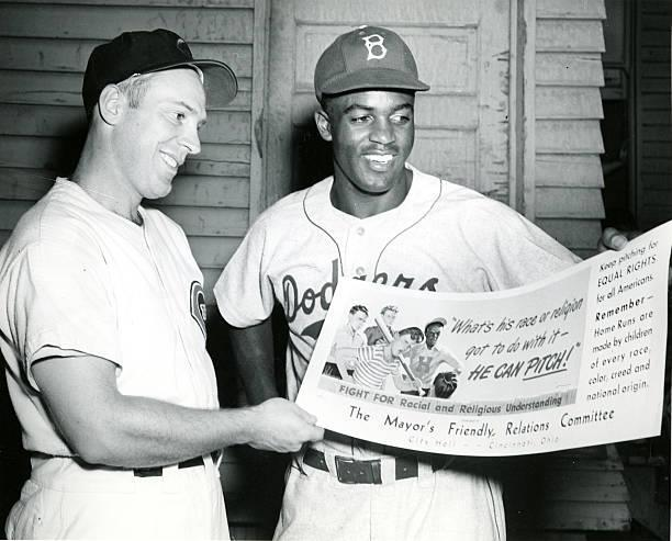 American baseball players Danny Litwhiler (left) of the Cincinnati Reds and Jackie Robinson (1919 - 1972) of the Brooklyn Dodgers pose together as they smile and hold a poster form the 'Mayor's Friendly Relations Committee,' Cincinnati, Ohio, May 11, 1984. The poster features an illustration of a group of boys and the text 'What's his race or religion go to do with it--he can pitch!', 'Fight for Racial and Religious Understanding', and 'Keep pitching for EQUAL RIGHTS for all Americans. Remember--Home Runs are made by children of every race, color, creed and national origin.' (Photo by Betz-Marsh Studio/Cincinnati Museum Center/Getty Images)