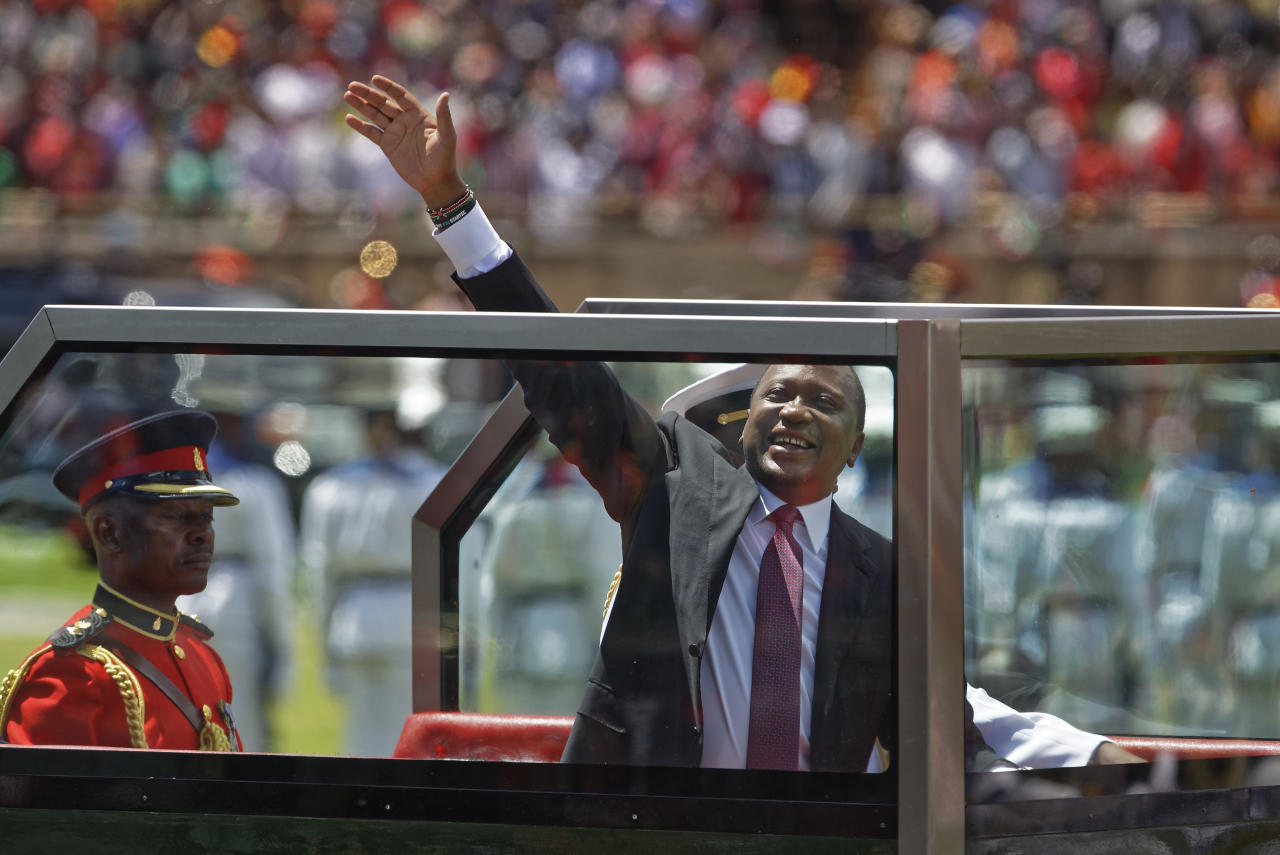 <p>Kenyan President Uhuru Kenyatta waves from behind bulletproof glass as he arrives for his inauguration ceremony at Kasarani stadium in Nairobi, Kenya Tuesday, Nov. 28, 2017. (Photo: Ben Curtis/AP) </p>