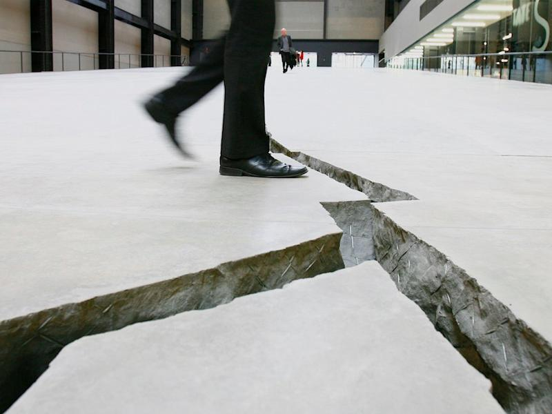 A man poses for the camera as he walks over Doris Salcedo's work, Shibboleth - a giant crack in the floor of the Tate Modern in London October 8, 2007. Colombian artist Doris Salcedo has filled Tate Modern's cavernous Turbine Hall with a hole as the latest work in the art gallery's annual installation series. Dubbed Shibboleth after the biblical massacre of the same name, the work is a trench dug into the concrete floor of the former power station and running its entire 167 metres length starting as a crack and ending as a chasm. (BRITAIN)