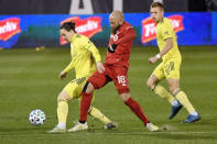 Toronto FC's Nick DeLeon, center, challenges Nashville SC's Alex Muyl, left, as Nashville's Alistair Johnston watches during the first half of an MLS soccer playoff match Tuesday, Nov. 24, 2020, in East Hartford, Conn. (AP Photo/Jessica Hill)