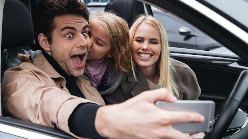 Young family taking selfie with phone in car