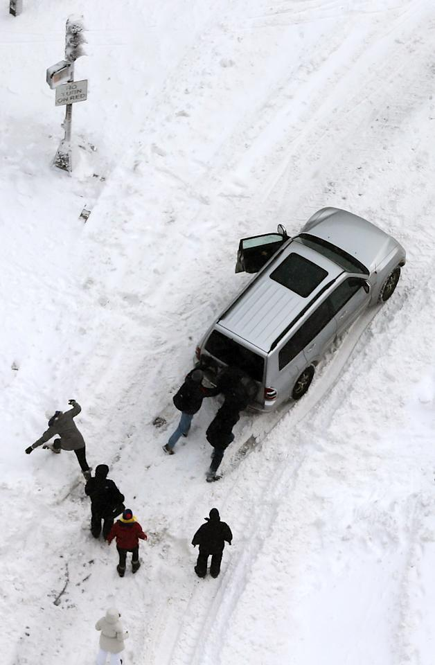 BOSTON, MA - FEBRUARY 09:  People attempt to push a stuck vehicle in the Back Bay neighborhood following a powerful blizzard on February 9, 2013 in Boston, Massachusetts. The storm knocked out power to 650,000 and dumped more than two feet of snow in parts of New England.  (Photo by Mario Tama/Getty Images)
