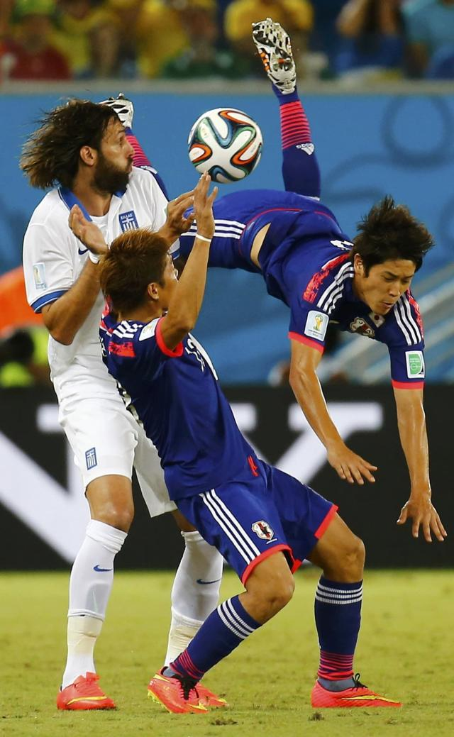 Japan's Atsuto Uchida (R) is fouled by Greece's Giorgios Samaras (L) as Japan's Yoshito Okubo reacts during their 2014 World Cup Group C soccer match at the Dunas arena in Natal June 19, 2014. REUTERS/Kai Pfaffenbach (BRAZIL - Tags: SOCCER SPORT WORLD CUP)
