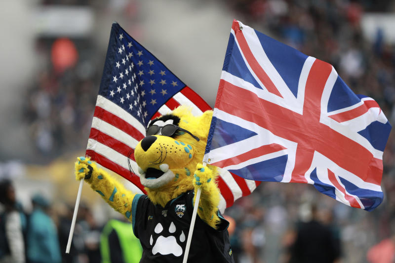 The Jacksonville Jaguars mascot carries the flags of the United States and Great Britian ahead of an NFL football game between the Houston Texans and the Jacksonville Jaguars, at Wembley Stadium, Sunday, Nov. 3, 2019, in London. (AP Photo/Ian Walton)