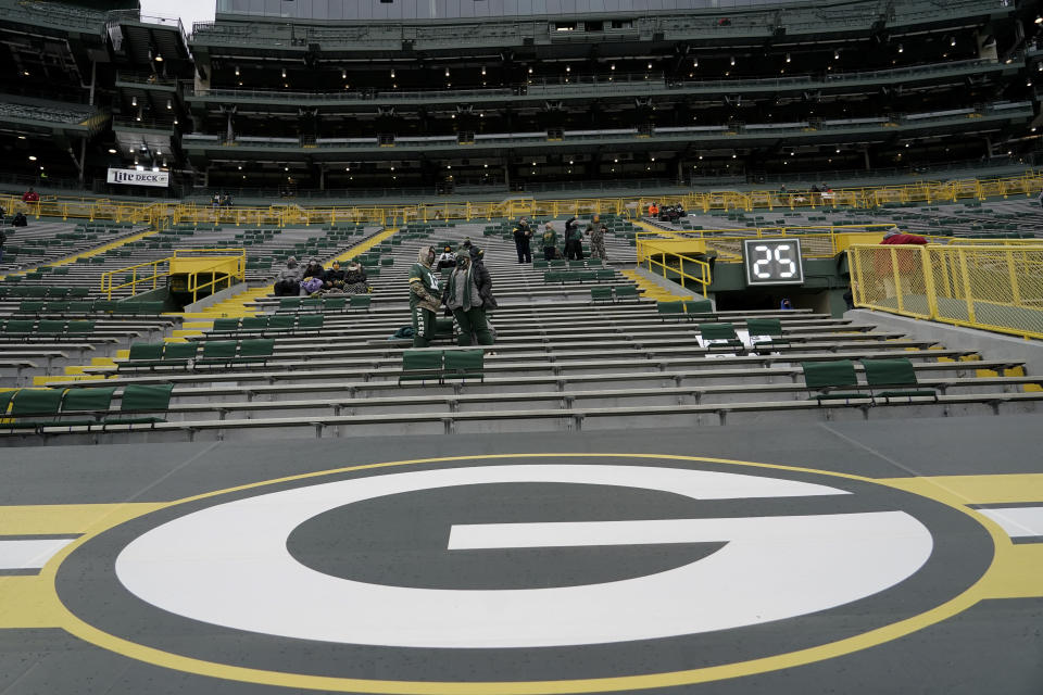 Fans take their socially distanced seats before an NFL divisional playoff football game between the Los Angeles Rams and Green Bay Packers, Saturday, Jan. 16, 2021, in Green Bay, Wis. (AP Photo/Morry Gash)
