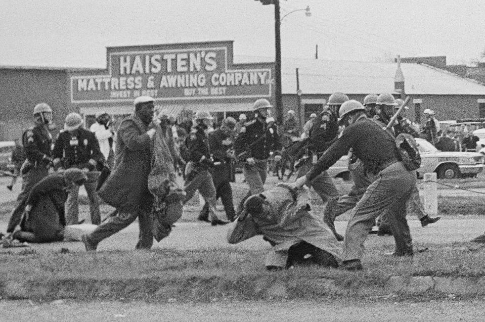 FILE - In this March 7, 1965, file photo, a state trooper swings a billy club at John Lewis, right foreground, chairman of the Student Nonviolent Coordinating Committee, to break up a civil rights voting march in Selma, Ala. The March 7, 2021, Selma Bridge Crossing Jubilee will be the first without the towering presence of Lewis, as well as the Rev. Joseph Lowery, the Rev. C.T. Vivian and attorney Bruce Boynton, who all died in 2020. (AP Photo/File)