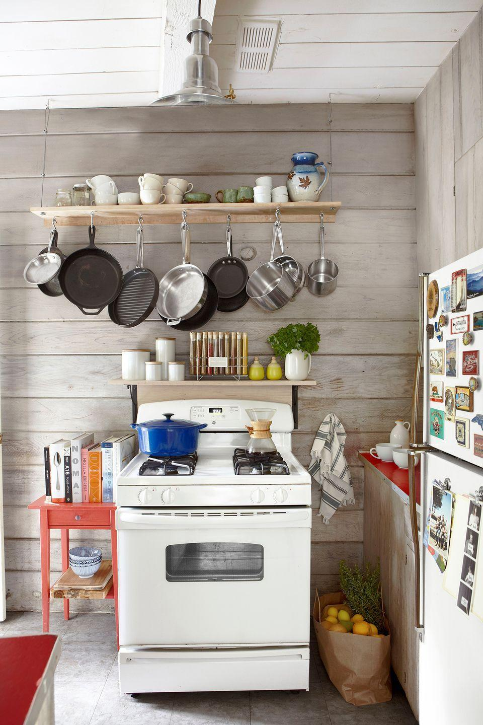 <p>Light-colored wood panels give this retro-style kitchen a cocoon-like feel.</p>