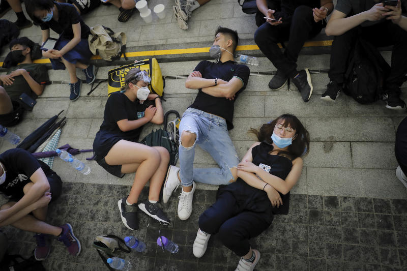 Protesters take a rest near the Legislative Council after staged a massive protest against the unpopular extradition bill in Hong Kong, Monday, June 17, 2019. Protesters in Hong Kong have left the streets, averting possible clashes with police by moving to areas near the city's government headquarters. (AP Photo/Kin Cheung)