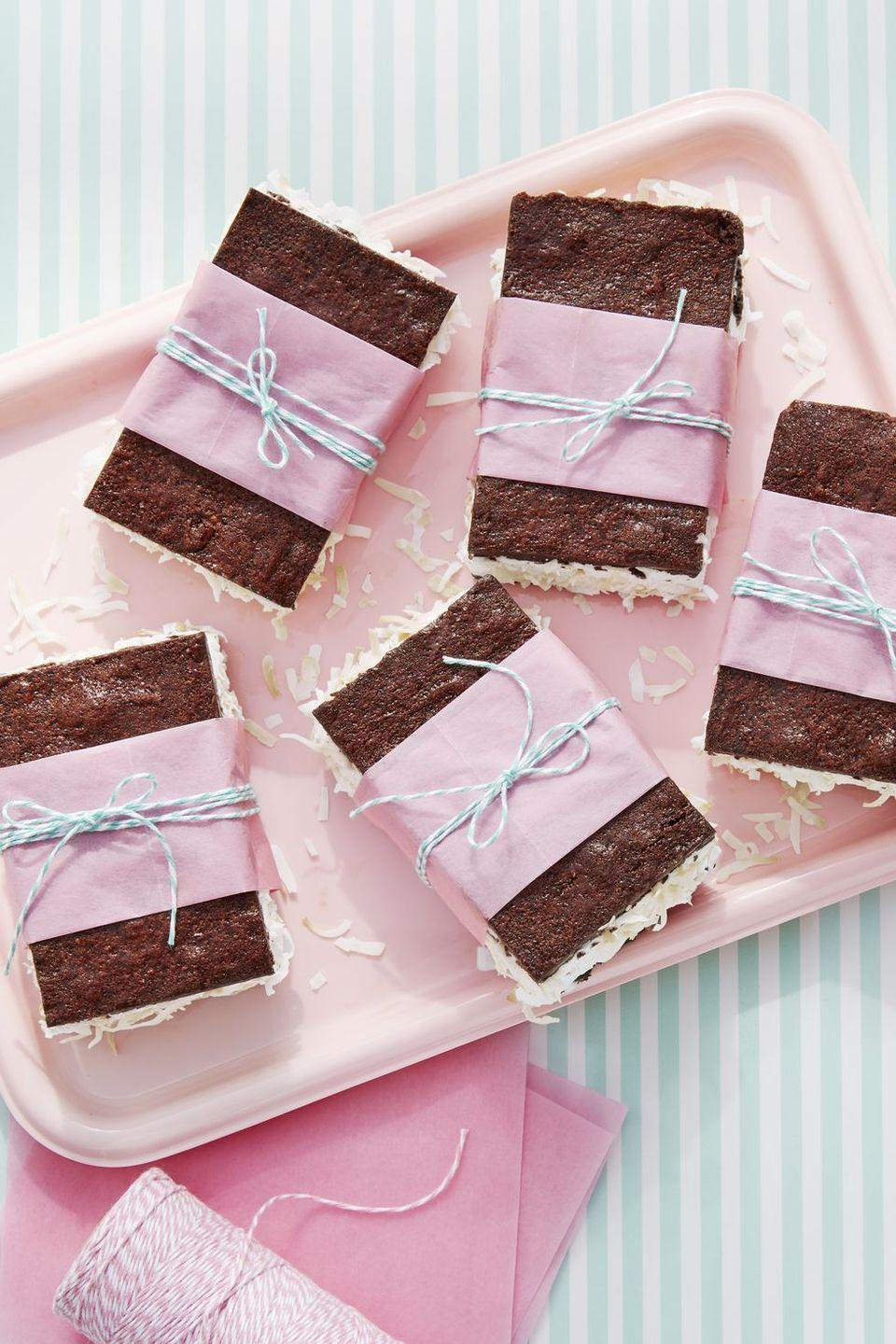 "<p>Coconut gelato is the star of these brownie bites.</p><p><strong><a href=""https://www.countryliving.com/food-drinks/a20747923/chewy-brownie-ice-cream-sandwiches-recipe/"" rel=""nofollow noopener"" target=""_blank"" data-ylk=""slk:Get the recipe"" class=""link rapid-noclick-resp"">Get the recipe</a>.</strong></p><p><strong><a class=""link rapid-noclick-resp"" href=""https://www.amazon.com/USA-Pan-Bakeware-Resistant-Aluminized/dp/B00282JL7G/?tag=syn-yahoo-20&ascsubtag=%5Bartid%7C10050.g.1138%5Bsrc%7Cyahoo-us"" rel=""nofollow noopener"" target=""_blank"" data-ylk=""slk:SHOP BAKING PANS"">SHOP BAKING PANS</a><br></strong></p>"