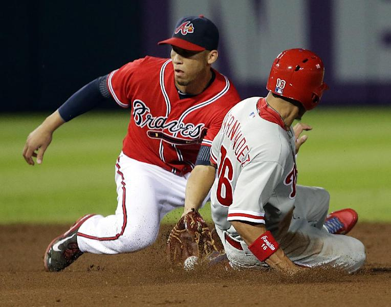 Atlanta Braves' Andrelton Simmons, left, catches the throw from Evan Gattis to tag out Philadelphia Phillies' Cesar Hernandez as he attempts to steal second base in the sixth inning of a baseball game, Friday, Sept. 27, 2013, in Atlanta. (AP Photo/David Goldman)