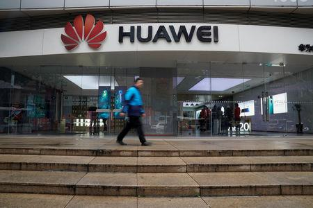 A man walks by a Huawei logo at a shopping mall in Shanghai