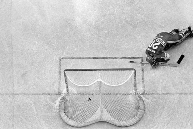 In this Feb. 22, 1980, file photo, Soviet Union hockey goalie Vladislav Tretiak falls to the ice as a goal is scored by U.S. player Mark Johnson (not shown) in the first period of a medal round match at the 1980 Winter Olympics in Lake Placid, N.Y. The U.S. defeated the Soviets 4-3. (AP Photo/Harry Cabluck, File)
