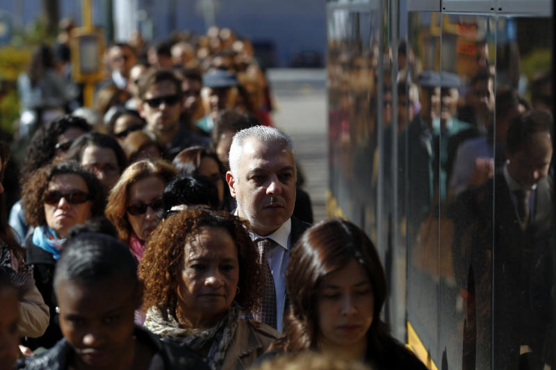Commuters queue for a bus during a 24-hour subway workers strike, Lisbon, Thursday, May 30, 2013. The strike snarled rush-hour traffic in the Portuguese capital in the latest protest against the bailed-out country's austerity policies. Unions representing subway workers called the walkout Thursday over labor reforms and cuts in entitlements. The government is enacting those measures in return for a euro 78 billion (USD101 billion) financial rescue two years ago. (AP Photo/Francisco Seco)