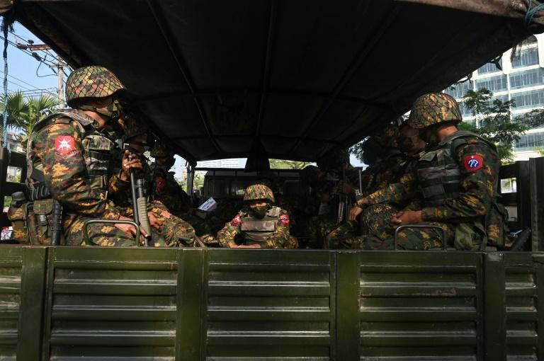 Soldiers sit in an army truck in Yangon