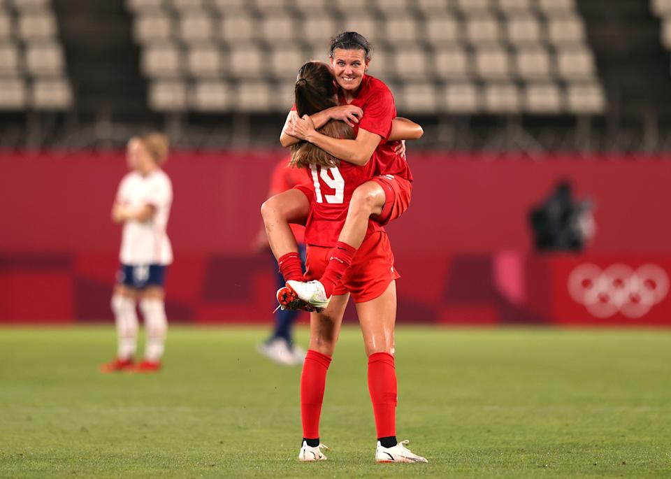 KASHIMA, JAPAN - AUGUST 02: Christine Sinclair #12 of Team Canada jumps on team mate Jordyn Huitema #19 of Team Canada following their side's victory in the Women's Semi-Final match between USA and Canada on day ten of the Tokyo Olympic Games at Kashima Stadium on August 02, 2021 in Kashima, Ibaraki, Japan. (Photo by Naomi Baker/Getty Images)