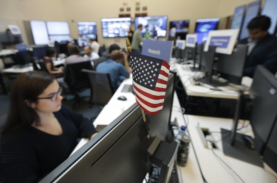 A flag of the United State is shown between monitors as workers sit at their desks during a demonstration in the war room, where Facebook monitors election related content on the platform, in Menlo Park, Calif., Wednesday, Oct. 17, 2018. (AP Photo/Jeff Chiu)