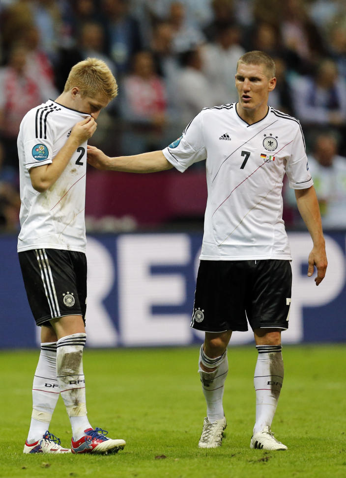 Germany's Marco Reus, left, and Bastian Schweinsteiger leave the pitch after the Euro 2012 soccer championship semifinal match between Germany and Italy in Warsaw, Poland, Thursday, June 28, 2012. (AP Photo/Matthias Schrader)