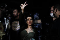 A woman flashes a V sign as police break up a social gathering during an operation against illegal and clandestine gatherings that authorities believe are partly responsible for fueling the spread of COVID-19, at a party hall in Sao Paulo, Brazil, early Saturday, April 17, 2021. (AP Photo/Marcelo Chello)
