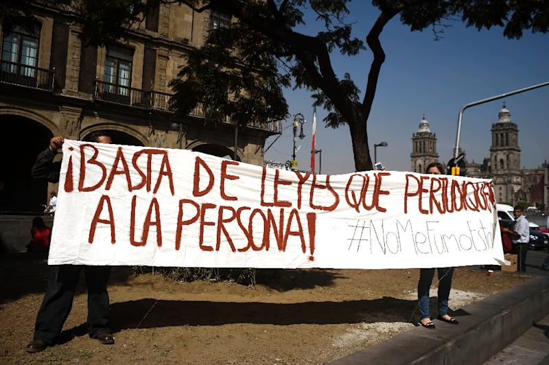"""People demonstrate against the decriminalization of marijuana with a banner reading """"Enough of laws which are detrimental to people"""" in front of the Supreme Court of Justice in Mexico City on November 4, 2015 (AFP Photo/Alfredo Estrella)"""