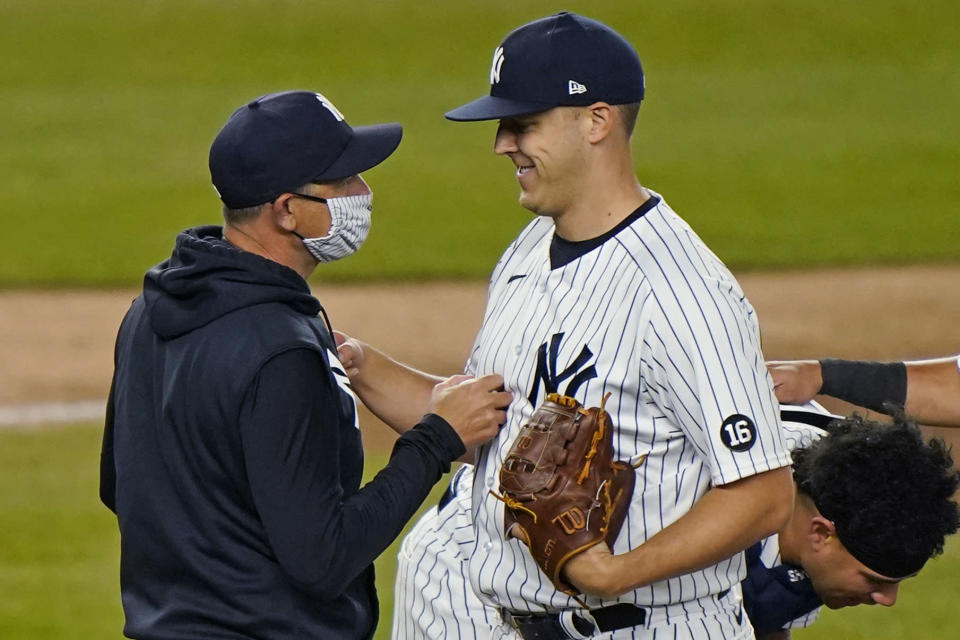 New York Yankees starting pitcher Jameson Taillon smiles after giving the ball to manager Aaron Boone, left, during the fifth inning of the team's baseball game against the Baltimore Orioles, Wednesday, April 7, 2021, at Yankee Stadium in New York. Taillon made his first start in the majors since May 1, 2019. (AP Photo/Kathy Willens)