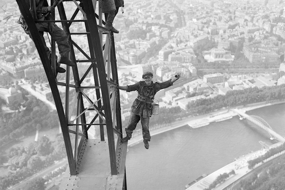 Workmen are shown at the top of the Eiffel Tower, putting on the final brushstrokes of a massive repainting project.