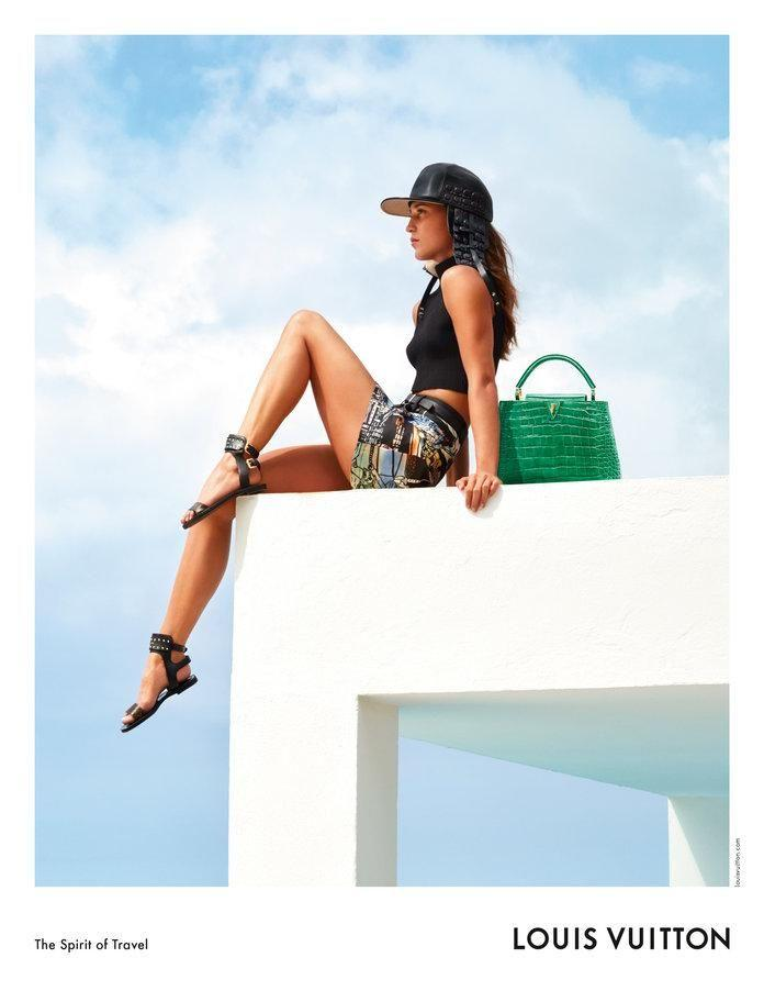 The 29-year-old is seen wearing black hat and printed mini-shorts hanging off the top of a building. Source: Louis Vuitton
