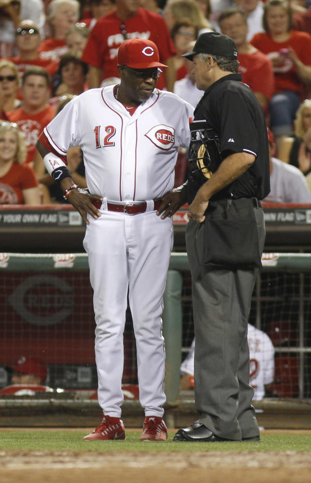 Cincinnati Reds manager Dusty Baker, left, has words with home plate umpire Gary Darling, right, over a Brandon Phillips strike out in the seventh inning during a baseball game against the Arizona Diamondbacks, Monday, Aug. 19, 2013, in Cincinnati. The Reds won 5-3. (AP Photo/David Kohl)