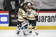 Boston Bruins center Patrice Bergeron (37) and goaltender Tuukka Rask (40) react as they leave the ice after Game 5 of an NHL hockey Stanley Cup first-round playoff series against the Washington Capitals, Sunday, May 23, 2021, in Washington. The Bruins won 3-1. (AP Photo/Nick Wass)