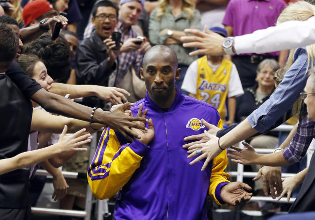 Los Angeles Lakers guard Kobe Bryant walks past fans before the second half of their NBA basketball game against the Utah Jazz in Salt Lake City, Utah, November 7, 2012. REUTERS/Jim Urquhart (UNITED STATES - Tags: SPORT BASKETBALL TPX IMAGES OF THE DAY)