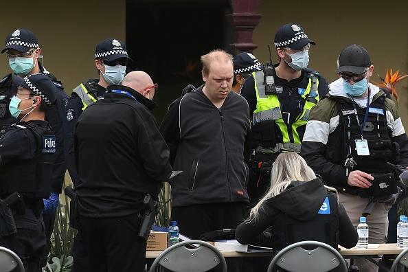 Police detain a protester during an anti-lockdown rally in Melbourne.