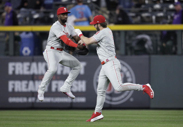 Philadelphia Phillies right fielder Bryce Harper, right, dunks his glove into the arms of Phillies center fielder Andrew McCutchen (22) after beating the Colorado Rockies in a baseball game in Denver, Saturday, April 20, 2019. Philadelphia won 8-5.(AP Photo/Joe Mahoney)