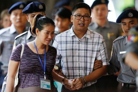 Detained Reuters journalist Wa Lone walks with his wife Pen ei mon as he arrives at Insein court in Yangon