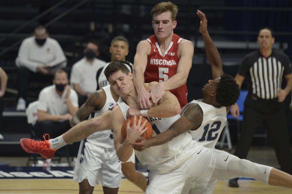 Penn State's John Harrar, center, gets tangled up with teammate Izaiah Brockington (12) as Wisconsin's Tyler Wahl (5) fouls him from behind in the second half of an NCAA college basketball game, Saturday, Jan. 30, 2021, in State College, Pa. (AP Photo/Gary M. Baranec)