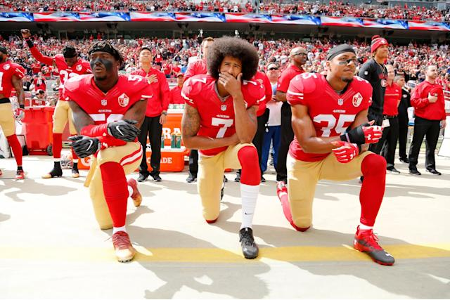 Colin Kaepernick kneels during the national anthem with fellow San Francisco 49ers Eli Harold and Eric Reid: EPA