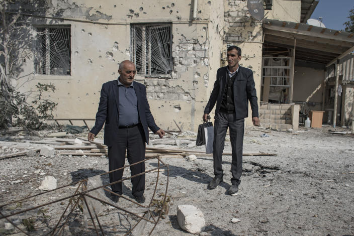 People inspect the damage following overnight shelling by Armenian forces, in the city of Terter, Azerbaijan, Thursday, Oct. 15, 2020. The conflict between Armenia and Azerbaijan continues for a third week despite a Russia-brokered cease-fire deal, as both sides exchanged accusations and claims of new attacks over the separatist territory of Nagorno-Karabakh. (Can Erok/DHA via AP)