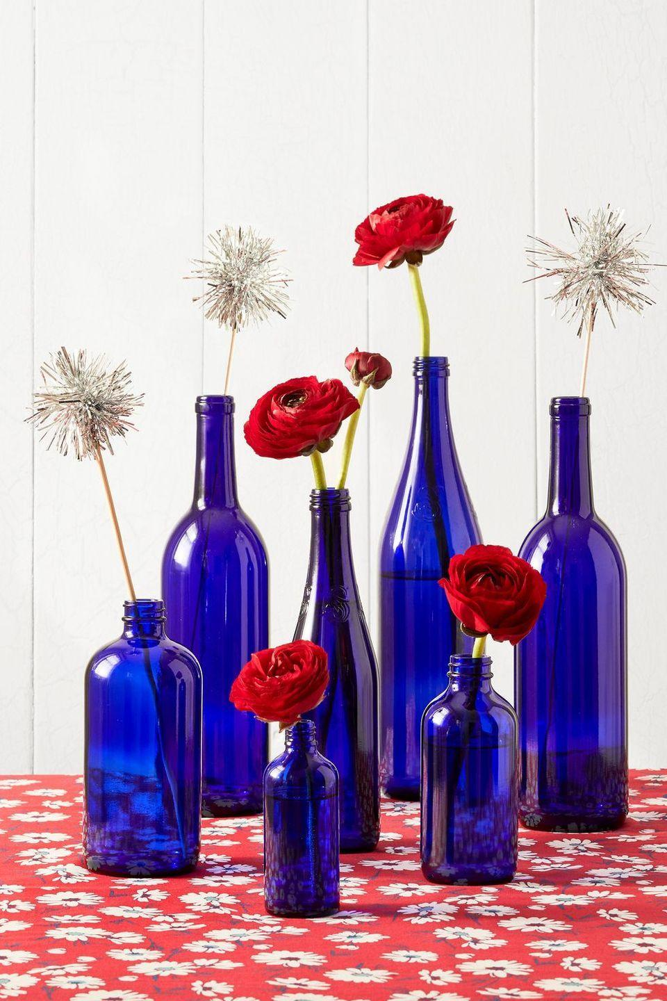 """<p>This easy decoration involves blue glass bottles, red flowers, and other 4th of July decorations, though it's easy enough to customize for just about any summer occasion. </p><p><a class=""""link rapid-noclick-resp"""" href=""""https://go.redirectingat.com?id=74968X1596630&url=https%3A%2F%2Fwww.walmart.com%2Fsearch%2F%3Fquery%3Dblue%2Bglass%2Bbottles&sref=https%3A%2F%2Fwww.thepioneerwoman.com%2Fjust-for-fun%2Fg36599700%2Fsummer-party-ideas%2F"""" rel=""""nofollow noopener"""" target=""""_blank"""" data-ylk=""""slk:SHOP BLUE GLASS BOTTLES"""">SHOP BLUE GLASS BOTTLES</a></p>"""