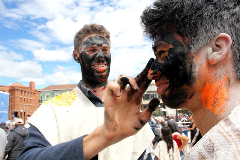 PASTO, COLOMBIA - JANUARY 05: Two men paint black each other's faces during Blacks' Day, 'Dia de los Negros', to commemorate the date when African slaves were free to indulge their playful outbursts as part of the 'Carnaval de Negros y Blancos' on January 05, 2019 in Pasto, Colombia. The festival was declared as one of the Masterpieces of the Oral and Intangible Heritage of Humanity by the UNESCO and is the most popular celebration in South Colombia. (Photo by Vizzor Image/Getty Images)