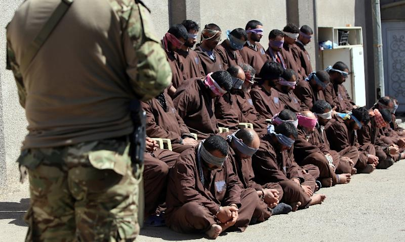A member of Iraqi secruity forces (L) guards 31 suspected Islamic State group members at the Iraqi Intelligence service's headquarters in Baghdad on March 16, 2015 (AFP Photo/Ali Al-Saadi)