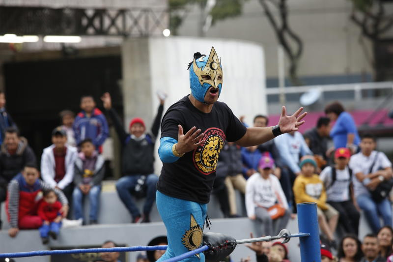 """Mexican wrestler Relampago Veloz encourages the crowd during a """"lucha libre"""" fight in Mexico City, Saturday, Dec. 21, 2019. Mexican wrestling, otherwise known as the """"lucha libre,""""  is a highly traditional form of light entertainment. (AP Photo/Ginnette Riquelme)"""