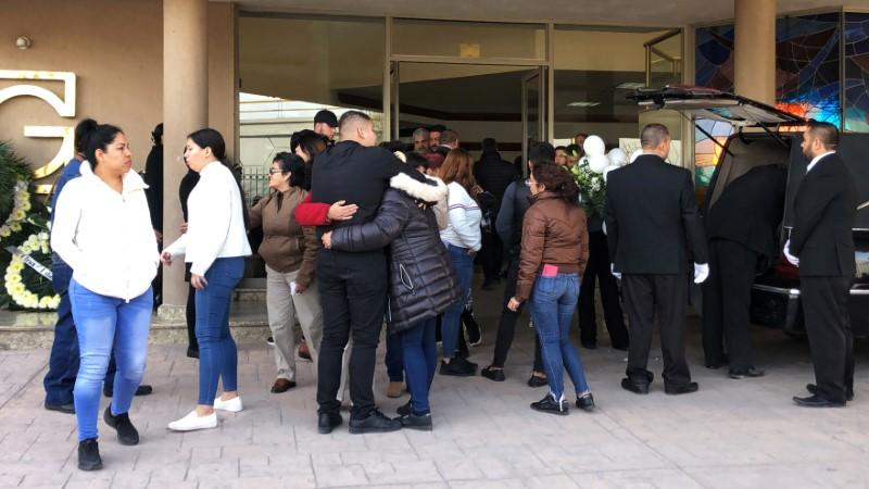 People hug each other next to the hearse with the remains of an 11-year-old boy that shot dead a teacher and wounded at least six others before killing himself, in Torreon