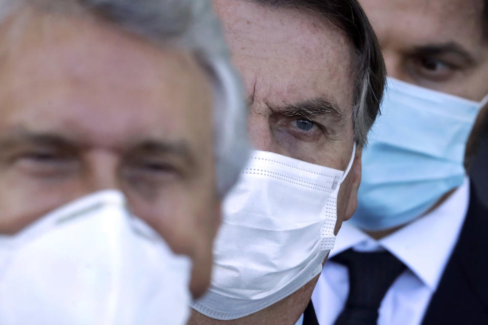 Brazilian President Jair Bolsonaro, center, arrives for a press conference following a meeting about the federal government's response to the COVID-19 pandemic at the presidential residence Alvorada Palace in Brasilia, Brazil, Wednesday, March 24, 2021. In recent weeks, Latin America's largest country has become the pandemic's global epicenter, with more deaths from the virus each day than in any other nation. (AP Photo/Eraldo Peres)
