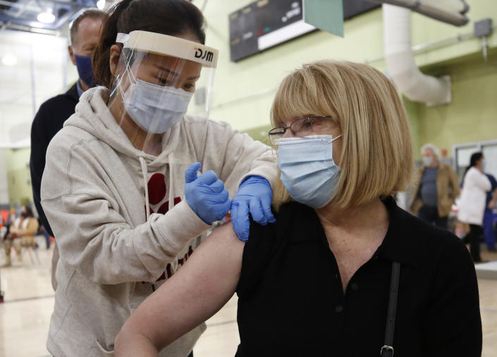 Pacoima Middle School teacher Abigail Abbott, 65, gets her COVID-19 vaccination from Nurse Practitioner Jiyoun Cho, left, as Los Angeles Unified employees received their first dose of the vaccine Wednesday morning. (Al Seib / Los Angeles Times via Getty Images).