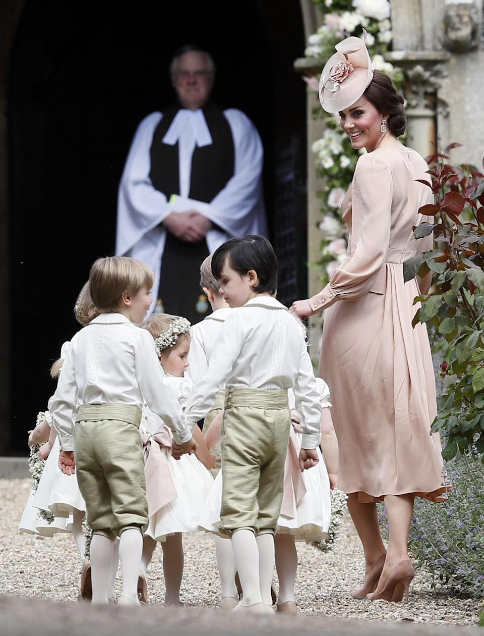 Kate made sure to not upstage her sister by wearing a dress from Alexander McQueen. The rose pink design was a midi style with a V-neck that she paired with a matching floral hat and suede heels. (Photo: PA)
