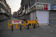 A Kashmiri man crosses a barricade set up as road blockade by paramilitary soldiers on the first anniversary of India's decision to revoke the disputed region's semi-autonomy, in Srinagar, Indian controlled Kashmir, Wednesday, Aug. 5, 2020. Last year on Aug. 5, India's Hindu-nationalist-led government of Prime Minister Narendra Modi stripped Jammu-Kashmir of its statehood and divided it into two federally governed territories. Late Tuesday, authorities lifted a curfew in Srinagar but said restrictions on public movement, transport and commercial activities would continue because of the coronavirus pandemic. (AP Photo/ Dar Yasin)