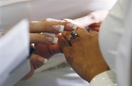 A woman puts a ring on the hand of another woman in a civil union ceremony after Colorado's civil union law went into effect in Denver